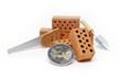 Ziegelsteine mit Minisäge und Euromünze