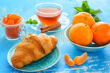cup of tea, croissant, and mandarines on blue background