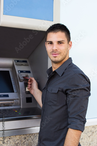 Handsome young man put his credit card at the ATM