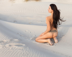Nude woman on sandy beach