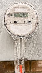 Modern digital electric meter covered in ice.