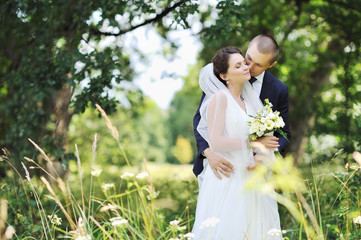 Beautiful kissing wedding couple. Outdoors portrait