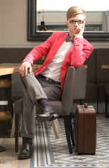 Young handsome stylish man with suitcase waits