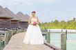Bride in wedding dress posing near the water villas