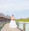 Bride in wedding dress posing near the water villas on a Maldive