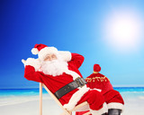 Santa Claus sitting on a chair and relaxing, on a beach