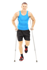 Full length portrait of an injured male athlete with crutches
