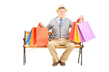 Smiling senior man seated on a wooden bench holding shopping bag