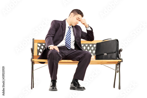 Worried young businessperson sitting on a wooden bench