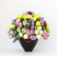 Colorful bunch of flowers in black vase