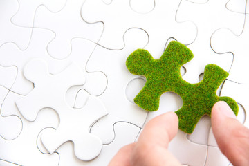 hand holding a green puzzle piece