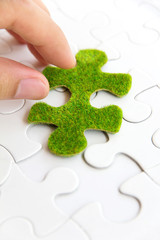 hand holding a green puzzle piece, green space concept