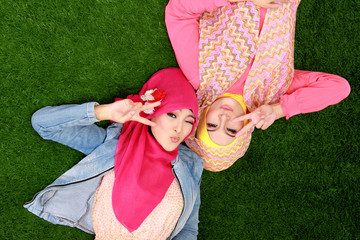 Two beautiful happy muslim woman smiling lying on grass