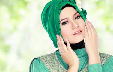Young beautiful muslim woman with green costume wearing hijab