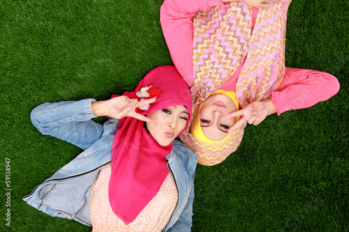 Two beautiful happy muslim woman smiling lying on grass