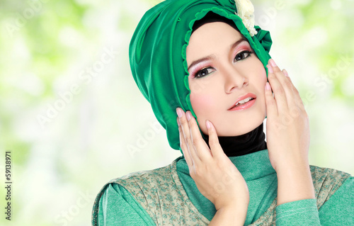 Young beautiful muslim woman with green costume wearing hijab