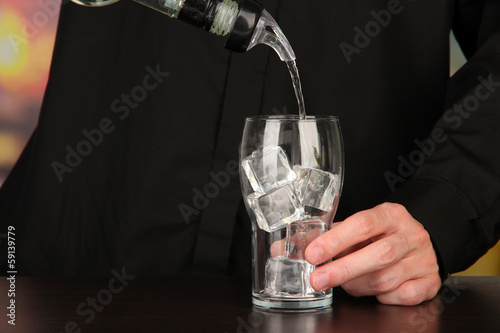 Bartender making cocktail on bright background, close-up