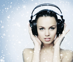 A pretty teenage girl listening to the music on the snow