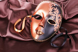 Mask on brown fabric background