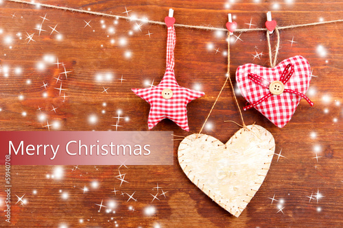 Decorative heart and star on rope, on wooden background