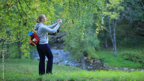 Woman taking pictures of nature scenes.