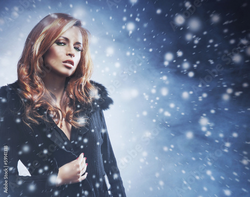 A sexy redhead Caucasian woman on a dark snowy background