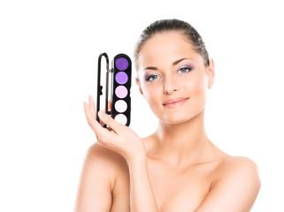 Beauty portrait of a young woman holding a makeup palette