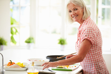 Middle Aged Woman Following Recipe On Digital Tablet