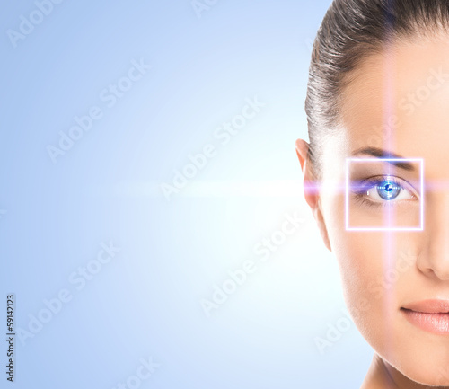 Close-up portrait of a young woman with a laser ray on her eye