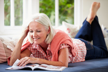 Middle Aged Woman Reading Magazine Lying On Sofa