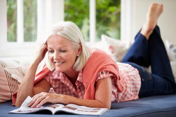 Middle Aged Woman Reading Magazine Lying On Sofa
