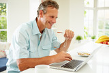 Middle Aged Man Using Laptop Over Breakfast