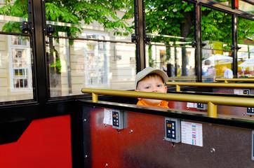 Cute little boy riding in a bus or tram