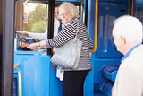 Senior Couple Boarding Bus And Using Pass