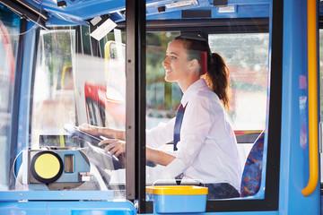 Portrait Of Female Bus Driver Behind Wheel