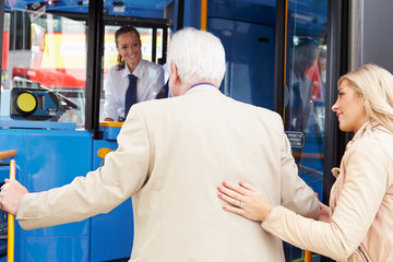 Woman Helping Senior Man To Board Bus