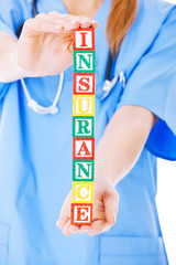 Nurse Holding Blocks Spelling Out Insurance Over White Backgroun