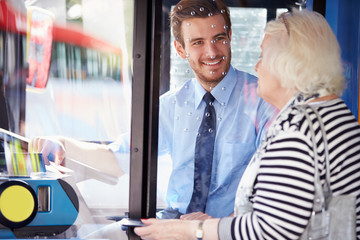 Senior Woman Boarding Bus And Buying Ticket