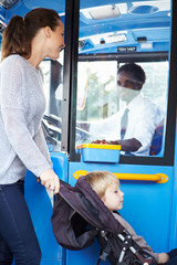 Mother With Child In Pushchair Boarding Bus
