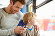 Father Using Mobile Phone On Bus Journey With Son - 59146122