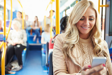 Woman Reading Text Message On Bus