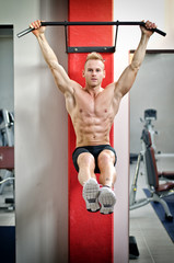 Young man hanging from gym equipment