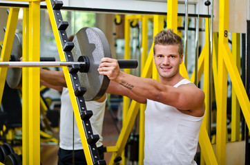 Smiling young man in gym putting weight disc on barbell