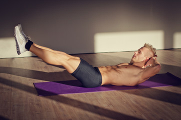Handsome young man doing abs exercises on mat