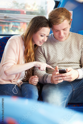 Teenage Couple Reading Text Message On Bus
