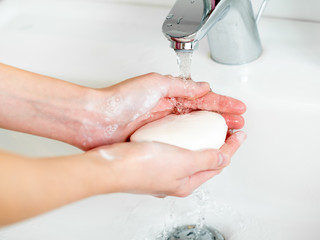 Washing of hands with soap in bathroom close up