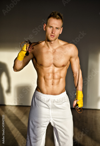 Shirtless muscular young man standing with jumping rope