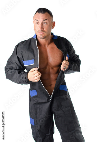 Bodybuilder mechanic opening coverall to show muscular body