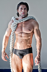 Muscular man nearly naked with heavy, big rope around neck