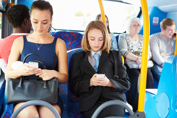 Passengers Sitting On Bus Sending Text Messages